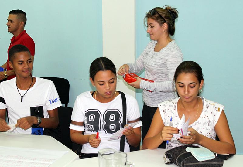 La Lic. en Derecho Elaine de la Paz Sarraf reparte un folleto con las nuevas regulaciones para el trabajo por cuenta propia en Cuba