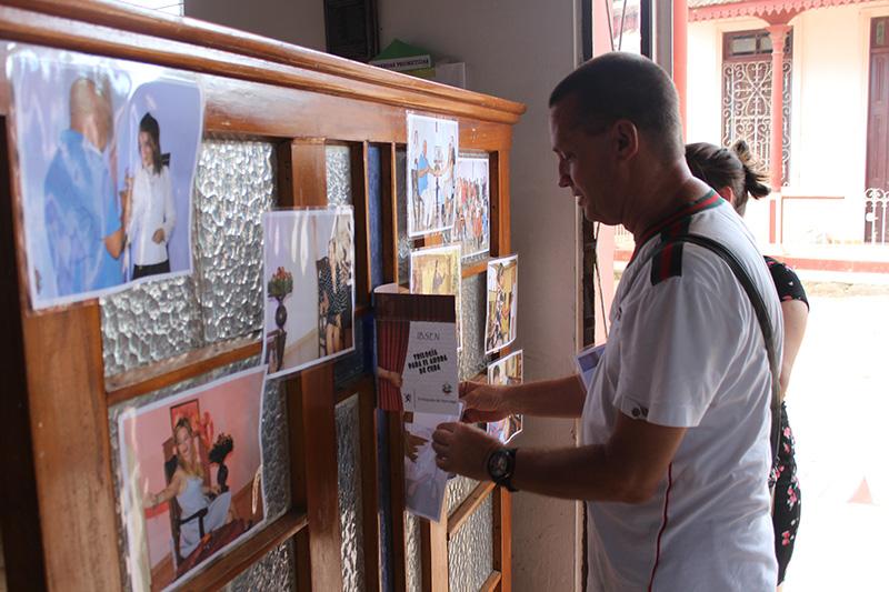 Roberto A. González, director de Trilogía para el ahora de Cuba, coloca algunas fotos y el programa antes de la puesta en escena en el municipio Los Palos